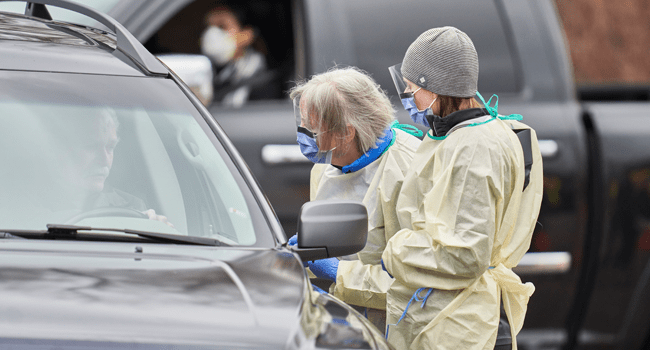In this file photo taken on March 17, 2020 health care workers speak with patients at a drive-thru Covid-19 assessment center in London, Ontario. Geoff Robins / AFP