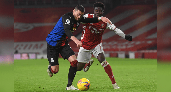 Crystal Palace's English defender Joel Ward (L) vies with Arsenal's English striker Bukayo Saka (R) during the English Premier League football match between Arsenal and Crystal Palace at the Emirates Stadium in London on January 14, 2021. NEIL HALL / POOL / AFP