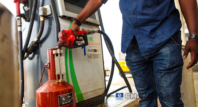 A file photo of a man filling up a measuring canister. Photo: Sodiq Adelakun/Channels Television