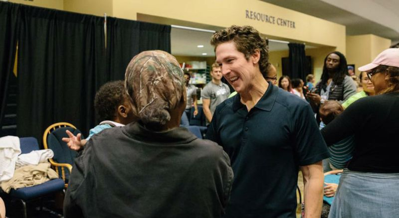 Joel Osteen speaks with refugees at Lakewood Church.