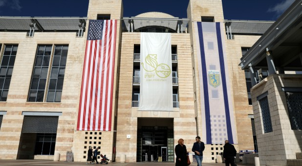 People walk at the Jerusalem's city hall as the American and Israeli national flags hang on the municipality building in Jerusalem.