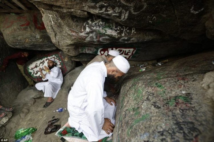 A Muslim pilgrim prays near rocks at the top of Noor Mountain, close to the entrance of Hira cave