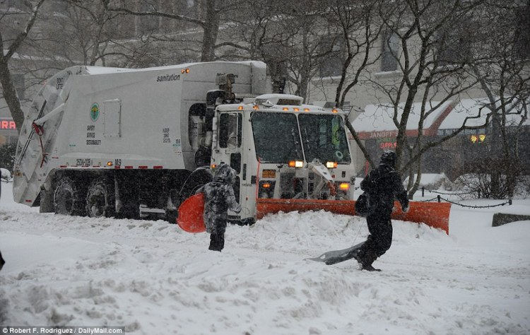 A parent and their child dragging sleds cross the road in Manhattan as a snow plow makes its way past on Saturday