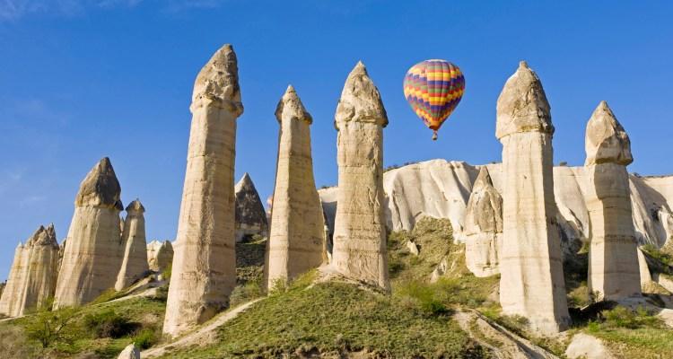 April 2008, Cappadocia, Turkey --- Hot Air balloon over Volcanic tufa rock pillars (Fairy Chimneys), Love Valley near Goreme, Cappadocia, Turkey --- Image by © Gavin Hellier/JAI/Corbis