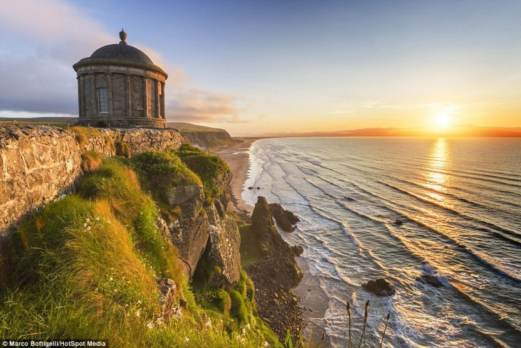 Tufts of long, untouched grass grow out of the rock face underneath the Mussenden Temple (above) in County Londonderry, Northern Ireland