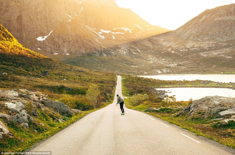 A man skateboarding down an empty road on Lofoten as the sun sets behind the mountain
