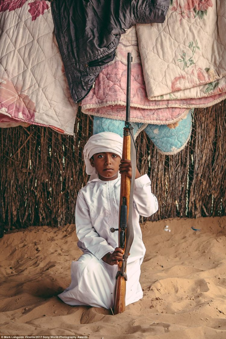 A bedouin boy in Oman poses with his father's rifle