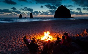 (Cannon Beach, Oregon) A family relaxes in front of Haystack Rock, the largest (72m) sea stack on the US coast.  This was the first day of fair weather in weeks on the coast, and the shoeline was dotted with small fires from groups enjoying the sunset. As usual with the people I seem to meet here, they all had relatives in Norway. Or at least these thought they did; as their name started with Mac... I said, sure, you might be Norwegian and took them up on their offer of a shoreside drink or five, to prove my ethnic heritage. I thus missed missed a very nice, partly cloudy post-rain photo op of some large rocks. Oh, well. At last the little girls thought I looked like Johnny Depp. As the Mad Hatter in Alice in Wonderland. I need a haircut.