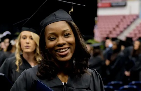 A smiling student walking out of CSU's graduation ceremony.
