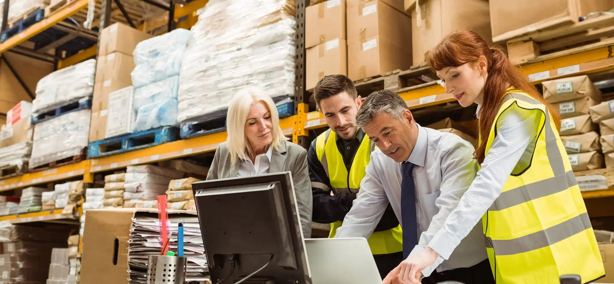 Warehouse managers and worker talking around a computer.