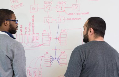 Two students staring at a white board with a diagram of connected computers and other technical systems.