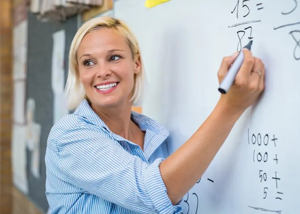 Smiling math teacher teaching addition on whiteboard in classroom. Smiling blonde woman explaining additions in column in class.