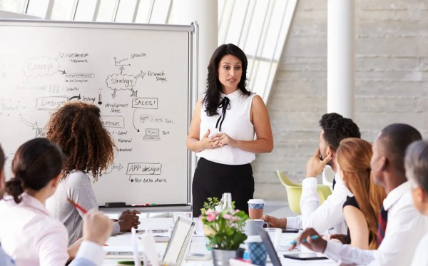 Businesswoman leading a meeting at a boardroom table in a bright room.