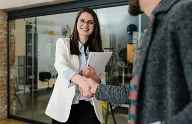 Woman with a resume in hand giving a handshake and smiling at a person about to interview her.