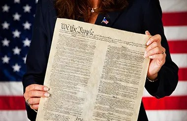 A female diplomat holding a copy of the U.S. constitution in front of the United States flag