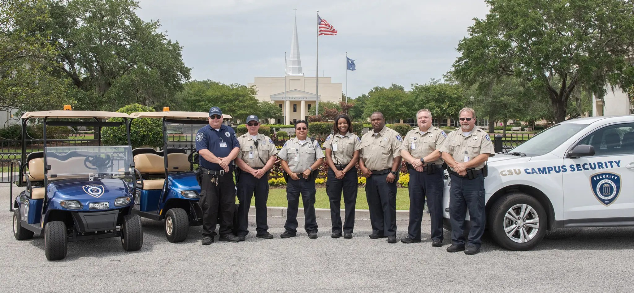 The CSU security team posing for the camera with a campus security vehicle and golf carts.