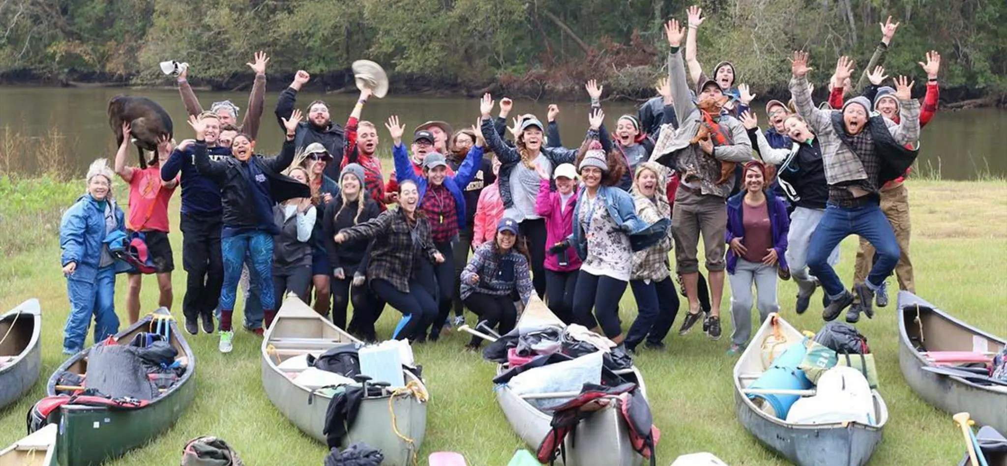 The Outdoor Adventure Club doing a fun group photo at a river with kayaks.