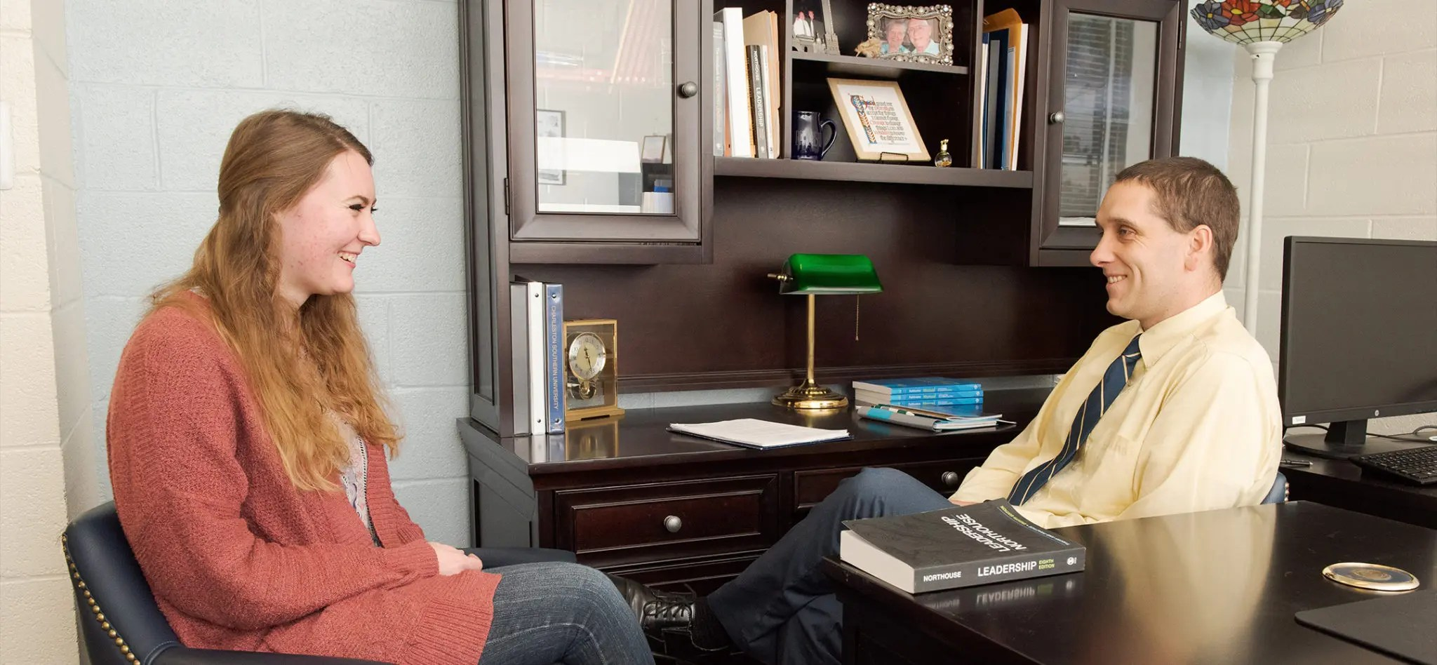 A faculty advisor sitting with a female student in his office talking about classes.