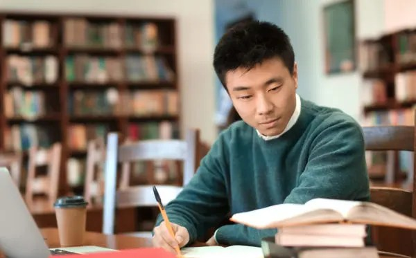 Asian student with laptop studying in library