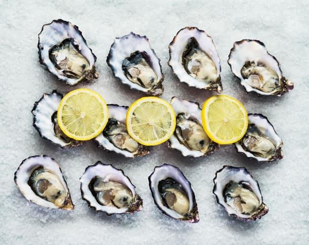 Dozen Fresh Oysters On A Sea Salt With Lemon Top View