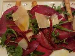 Little Italy, York, England, appetizer of Italian dried cured beef with parmesan shavings and rocket drizzled with EVOO and lemon juice