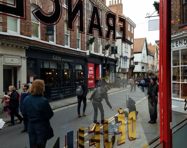 Watching a street entertainer throught the window of Cage Rouge at 52 Lower Petergate, in York, England.