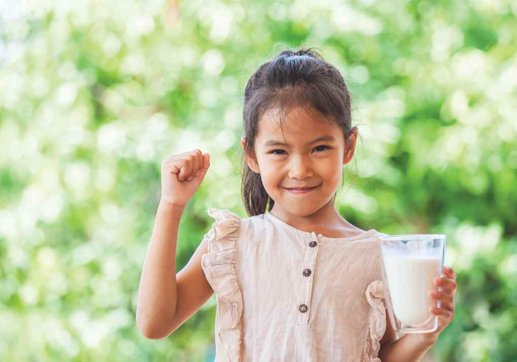 Young girl smiling with a big glass of milk