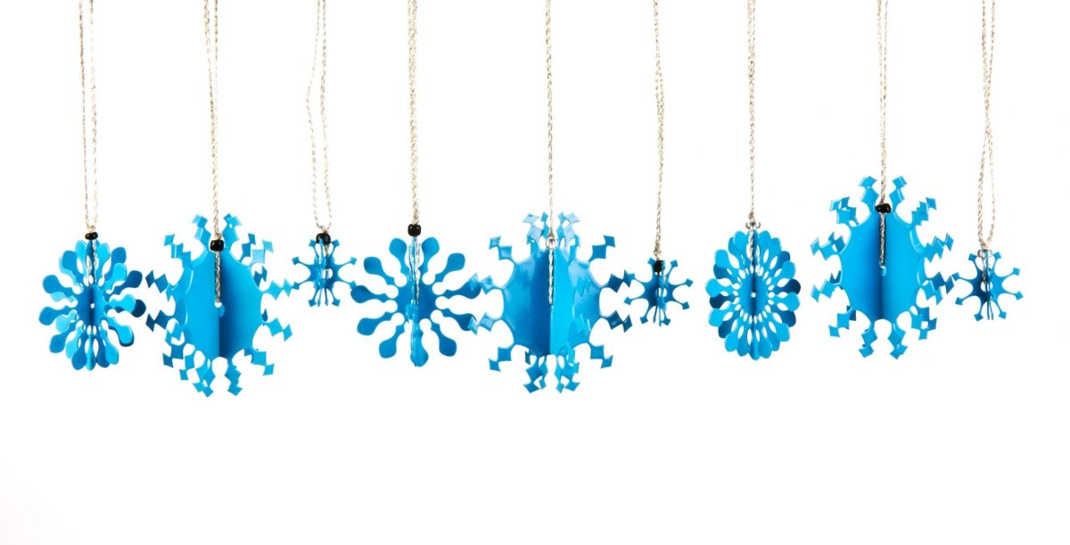 A collection of 3D metal snowflakes, some small, some medium and some large, coated in blue enamel paint each with a silver thread for hanging on the Christmas tree.