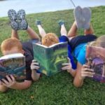 Get Kids Reading More Books - 3 Kids Lying On Grass Reading Harry Potter Books
