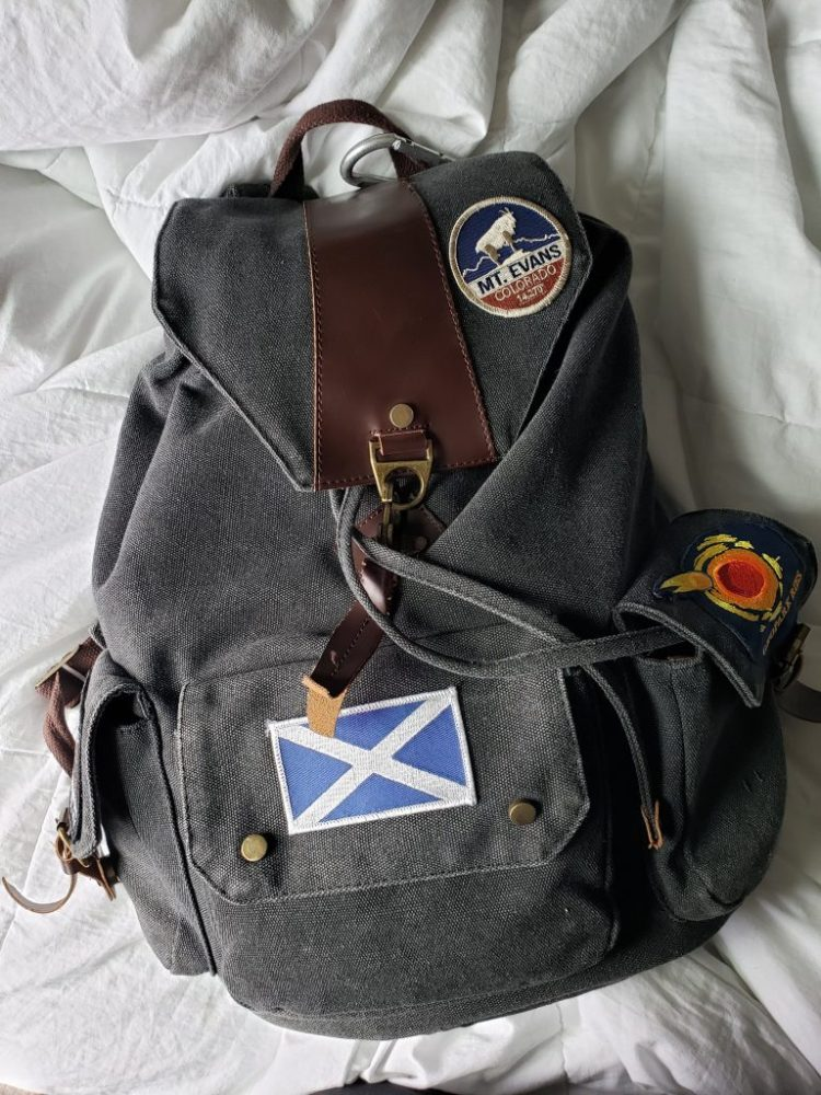 charcoal canvas backpack with patches sewn on