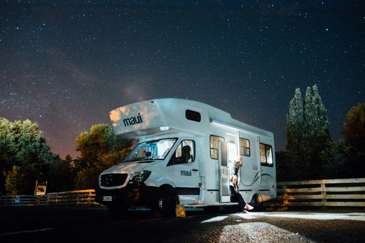 RV lit up at night with stars in empty parking lot