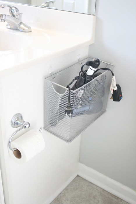 Wire basket filled with electrical appliances hanging to a bathroom counter.