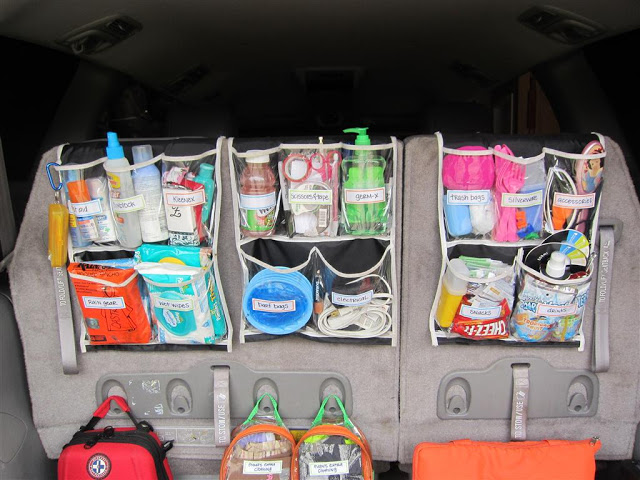 The trunk of a car organized neatly using shower caddies