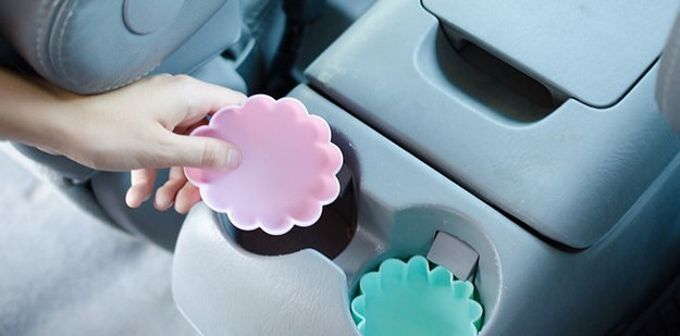 Two silicone cupcake holders being used as a car cleaning hack to keep dirt out from cup holders