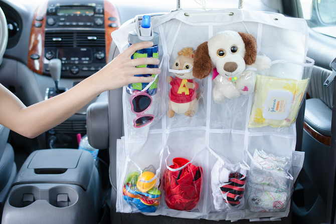 A clear shoe organizer filled with goodies overhanging the back of the car's passenger front seat