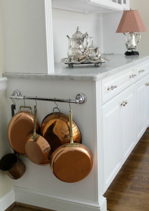 Pots and pans hanging on a towel bar.