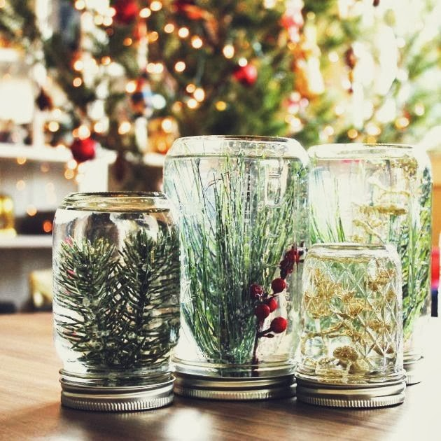 Four water-filled mason jars upside with faux garlands inside.