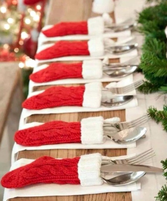 Mini Christmas stockings holding knives, spoons and forks on a table.