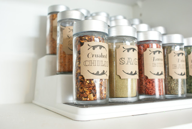 Spice bottles lined up in a row with custom labels on them.