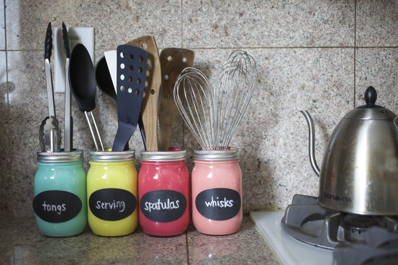 Four colorful mason jars with kitchen utensils stored inside.