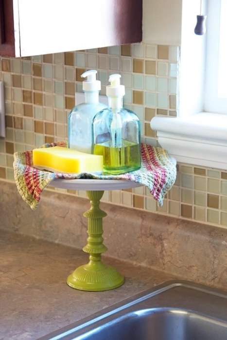 A cake stand on a kitchen countertop with dish soap and a sponge sat on it.