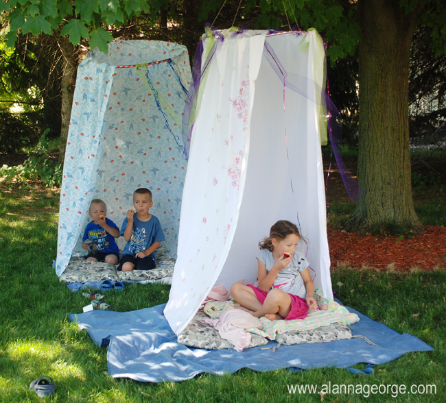 Two hula hoops attached to a tree branch with hanging linen to create hideouts for three toddlers.