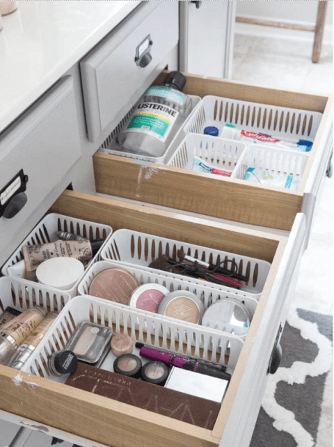 Open bathroom drawers organized with plastic trays.