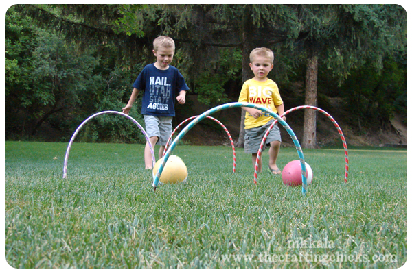 Hula hoops stuck in grass with two toddlers playing croquet.