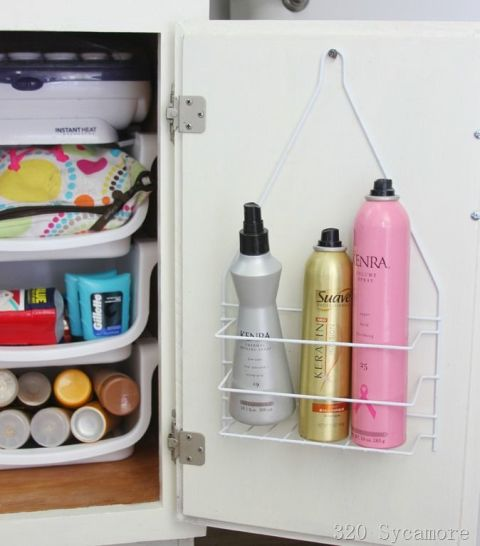 A wire frame hanging on a cabinet door holding toiletry bottles.