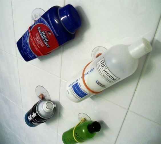 Toiletries attached to the bathroom wall with bands and suction cups.