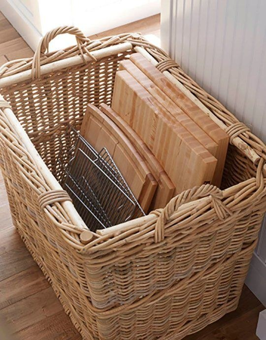 Cutting boards and wire trays stored in a wicker basket.