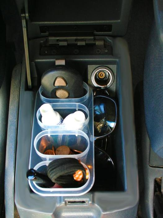 Ice pop maker tubs near the car's gear shift filled with odds and ends