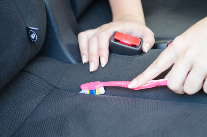 A toothbrush getting out dirt on a car seat