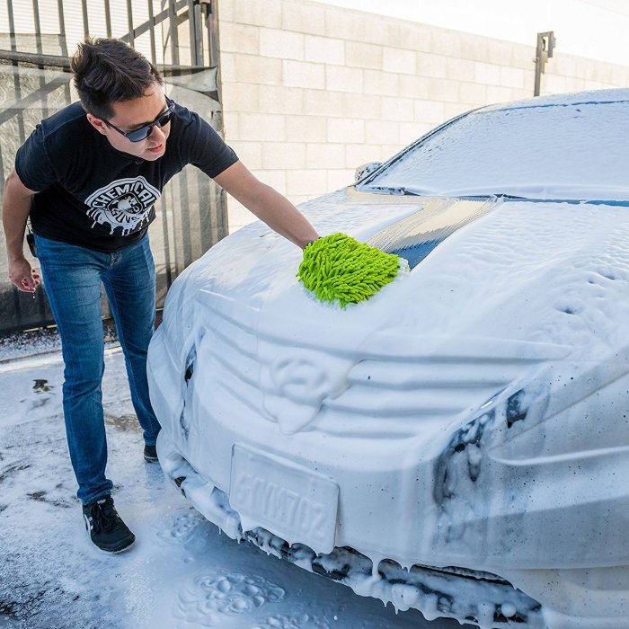 A man using a green microfiber mitt to clean his car